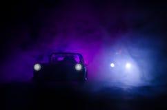 Polizeiwagen, der ein Auto nachts mit Nebelhintergrund jagt Polizeiwagen mit 911 Notfallschutzen, der zur Szene des Verbrechens b lizenzfreie stockfotos