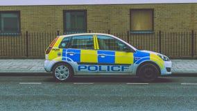 Polizeiwagen mit fehlender Radkappe parkte auf einer Straße Lizenzfreie Stockbilder