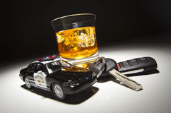 Polizeiwagen nahe bei alkoholischem Getränk und Tasten Lizenzfreie Stockbilder
