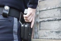 Poliziotta sulla pattuglia che controlla costruzione urbana. Immagini Stock