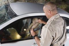 Poliziotto che batte la finestra di automobile Immagine Stock
