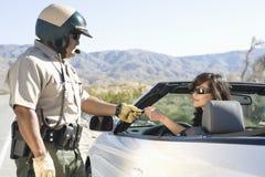 Poliziotto che controlla la licenza della donna Immagini Stock
