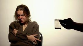 Poliziotto che mostra il pacchetto delle droghe che grida donna, prova psychical, ricerca fotografia stock