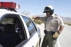 Poliziotto di traffico che guarda in automobile Fotografia Stock