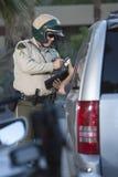 Poliziotto di traffico che riceve la carta di credito dal driver Immagine Stock
