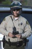 Poliziotto di traffico con la lavagna per appunti che sta contro l'automobile Fotografia Stock Libera da Diritti
