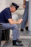 Poliziotto sulla sua seduta del telefono cellulare Fotografia Stock