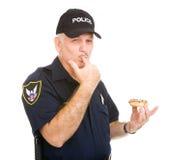 Polizist, der Finger leckt Stockbild