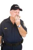 Polizist, der Krapfen isst Stockfoto