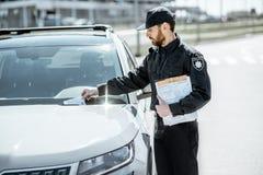 Polizist, der sich fein auf das Auto setzt lizenzfreie stockbilder
