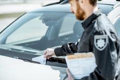 Polizist, der sich fein auf das Auto setzt lizenzfreie stockfotografie