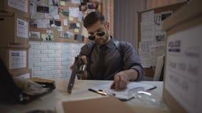 Polizist im Büro, welches das Gewehr auf Tabelle, Recht und Ordnung, Verbrecherüberfall auflädt stock footage
