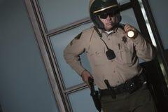 Polizist mit Taschenlampen-Zeichnungs-Gewehr vom Gurt Lizenzfreie Stockbilder