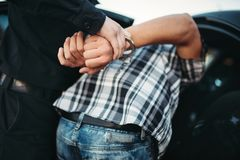 Polizist nimmt den Autodieb auf Straße fest lizenzfreies stockbild