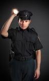 Polizist oder Sicherheitsbeamte, die eine Fackel glänzen Lizenzfreies Stockfoto