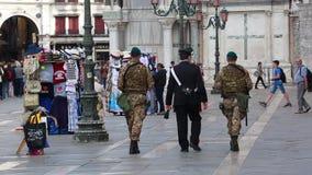Polizist und Militär mit Uniform auf Patrouille auf einem Quadrat in Venedig stock footage
