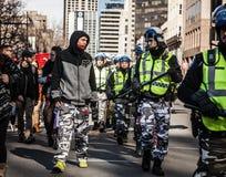 Polizist und Protestierender, die in den Augen und in der Abnutzung sich schauen Stockfotografie