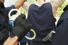 Polizisten, die Verbrecher festnehmen Lizenzfreie Stockfotos