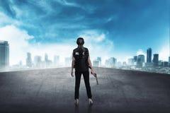 Polizistin, die auf der Gebäudedachspitze steht Lizenzfreie Stockfotos