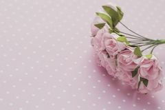Polka dot background. Pink decorative flowers. Close-up. Place for text.  royalty free stock photo