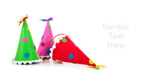 Polka-dot birthday hats on a white background. Green, pink and red birthday hats on a white background with copy space stock image