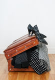 Polka dot clothing in a vintage leather suitcase. Black and white polka dot clothes and shoes in a vintage leather suitcase stock photography