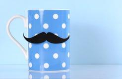 Polka dot coffee mug with mustache Stock Photos