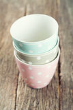 Polka dot cups. On wooden surface Stock Photos