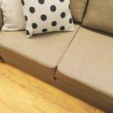 Polka dot cushion decorating a textile sofa Stock Images