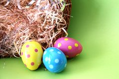 Polka dot Easter eggs lying in straw. Assortment of plastic polka dot Easter egg's next to a basket with staw royalty free stock photography