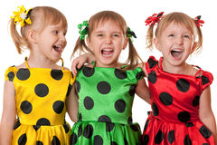 Polka dot fun. Three little girls in yellow, green and red polka dot dresses are laughing; isolated on the white background Stock Photography