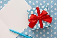 Polka dot gift box, blue pen and greeting card Royalty Free Stock Photo