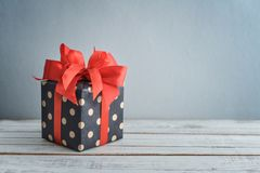 Polka dot Gift box with red ribbon. On blue background Royalty Free Stock Image