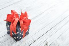 Polka dot Gift box with red ribbon. On white  wooden background Royalty Free Stock Images