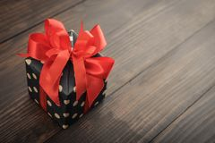 Polka dot Gift box with red ribbon. On wooden background closeup Royalty Free Stock Photography