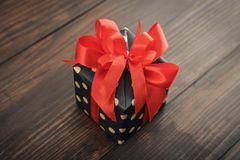 Polka dot Gift box with red ribbon. On wooden background closeup Stock Photography