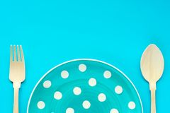 Polka dot plate with wooden spoon and fork on blue background