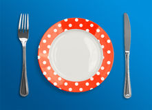 Polka dot red plate with fork and knife top view Stock Image