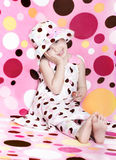 Polka dots heaven. Little girl dressed in polka dots dress with matching hat,leggings, and polka dots backdrop stock photography