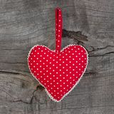 Polka dotted heart shape hanging on a wooden background for Vale royalty free stock photos