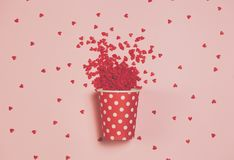 A polka dottet cup vith little hearts all around. Top view, flat lay. St. Valentine`s day concept stock image