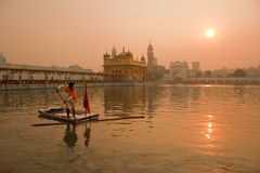 Poll Cleaner at the Golden Temple, Amritsar. A male cleaning the 'Amritsar' as the sun rises before the Guru Granth Sahib Is taken to the main temple Stock Photos