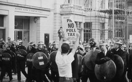 Poll Tax Riots, London. A protestor holds up a poster in front of riot police in St.Martins Place, London, England on March 31, 1990. The riot followed a march Stock Photo