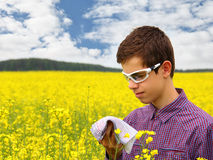 Pollen Allergy. Boy teenager in yellow canola field blowing his nose and suffering from pollen allergy. Glasses slightly protect the eyes from allergic stock photography