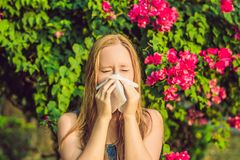 Pollen allergy concept. Young woman is going to sneeze. Flowering trees in background.  stock photography
