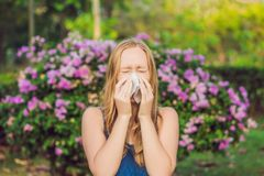 Pollen allergy concept. Young woman is going to sneeze. Flowering trees in background stock photos