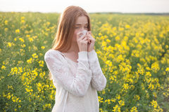 Pollen allergy, girl sneezing in a field of flowers.  Royalty Free Stock Image