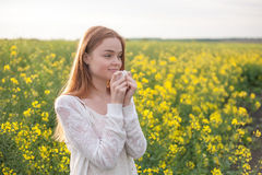Pollen allergy, girl sneezing in a field of flowers.  Stock Photo
