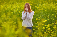 Pollen allergy, girl sneezing. In a field of flowers stock photo