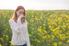 Pollen allergy, girl sneezing in a rapeseed field of flowers.  Stock Photos